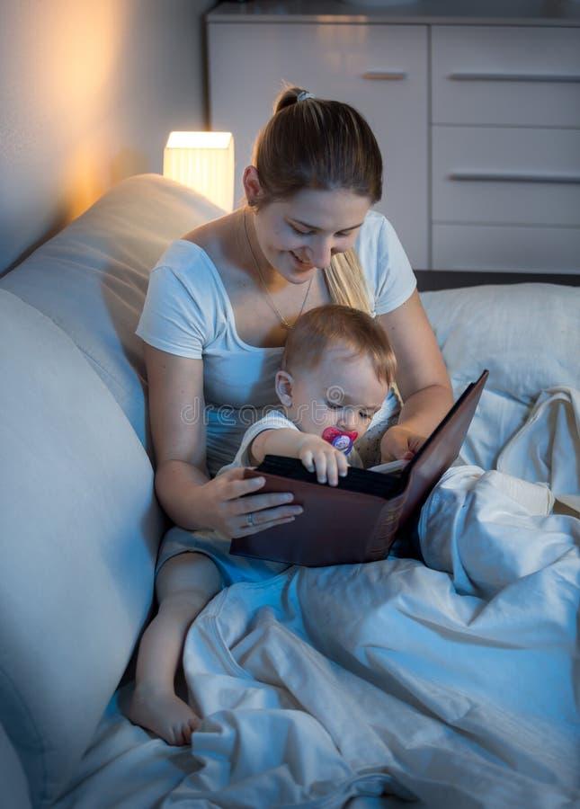 对她的婴孩的美丽的年轻母亲阅读书在床上在晚上 免版税库存图片