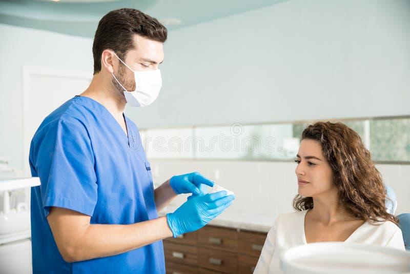 对妇女的牙医解释的牙齿模子诊所的 免版税库存图片