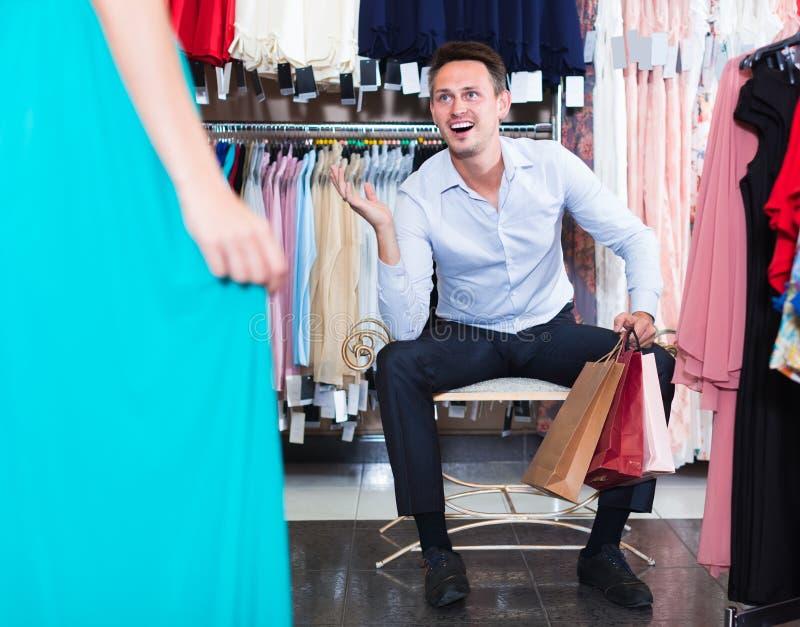 对妇女的年轻快乐的人给精品店穿衣 库存照片