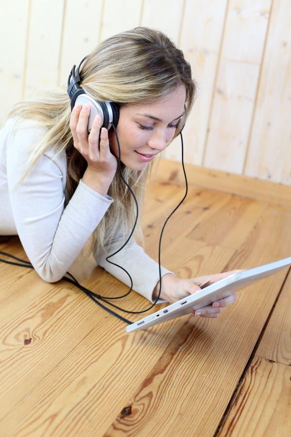 对妇女年轻人的耳机听的音乐 免版税库存图片