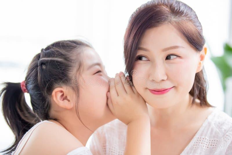 对妈妈的女儿耳语 免版税库存图片