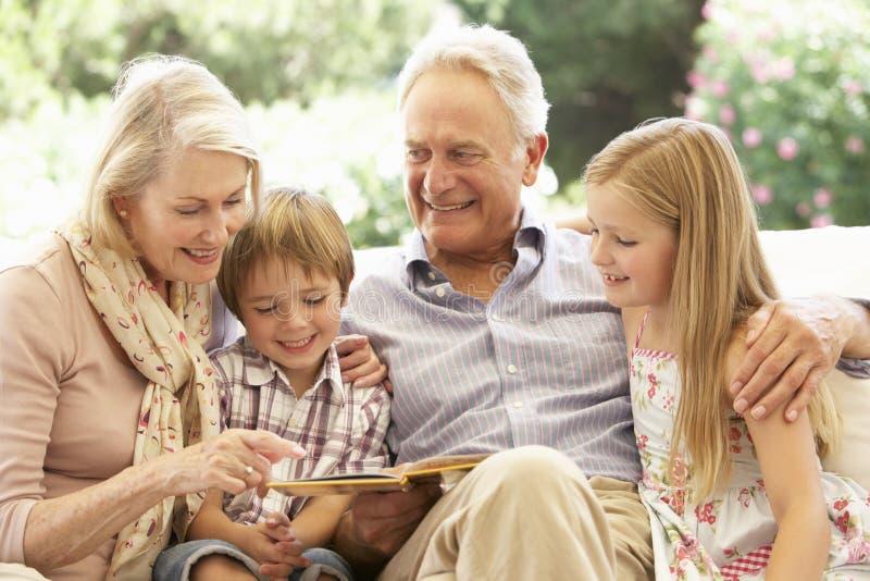 读对孙的祖父母画象在沙发 库存图片