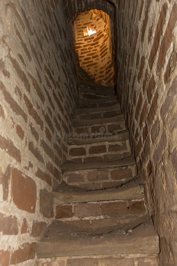 对导致钟楼的老教会的砖楼梯 库存图片