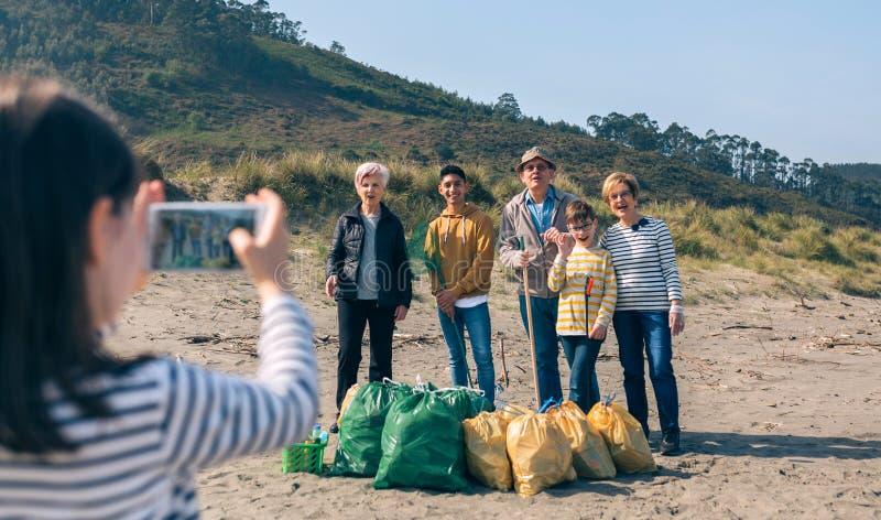 对小组的女孩照相志愿者在清洗海滩以后 免版税库存图片