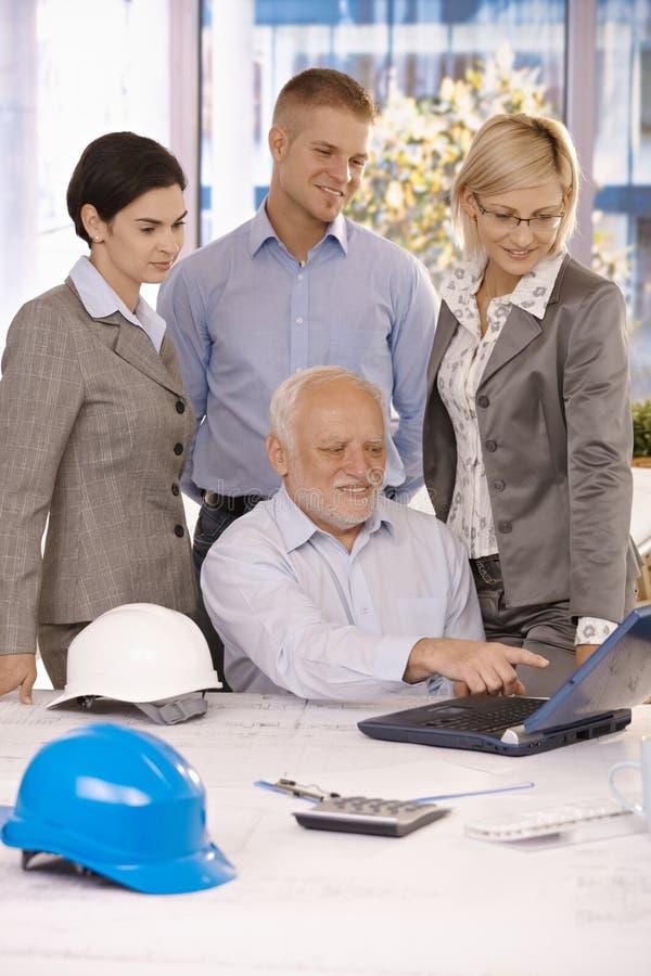 对小组的高级建筑师陈列工作在膝上型计算机 库存图片