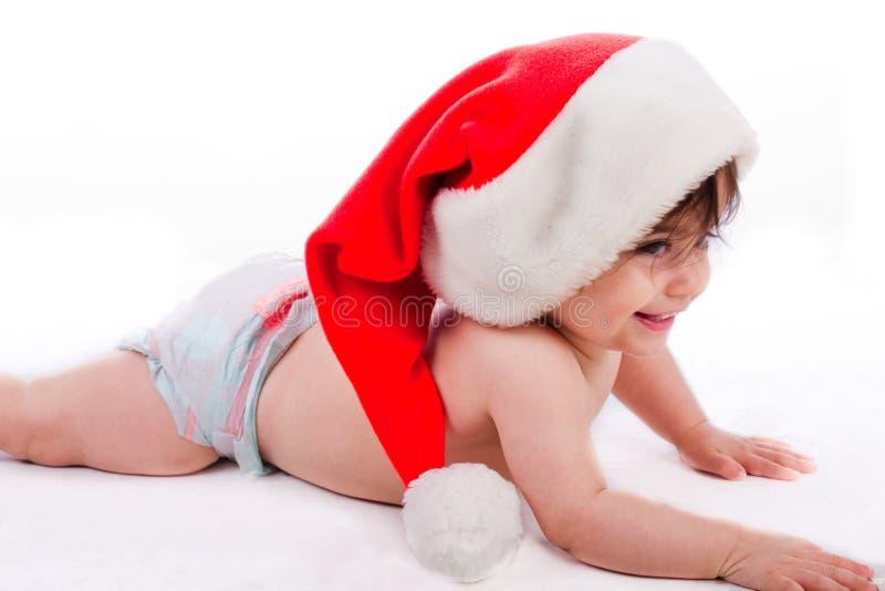 对尝试的婴孩爬行圣诞老人 库存图片