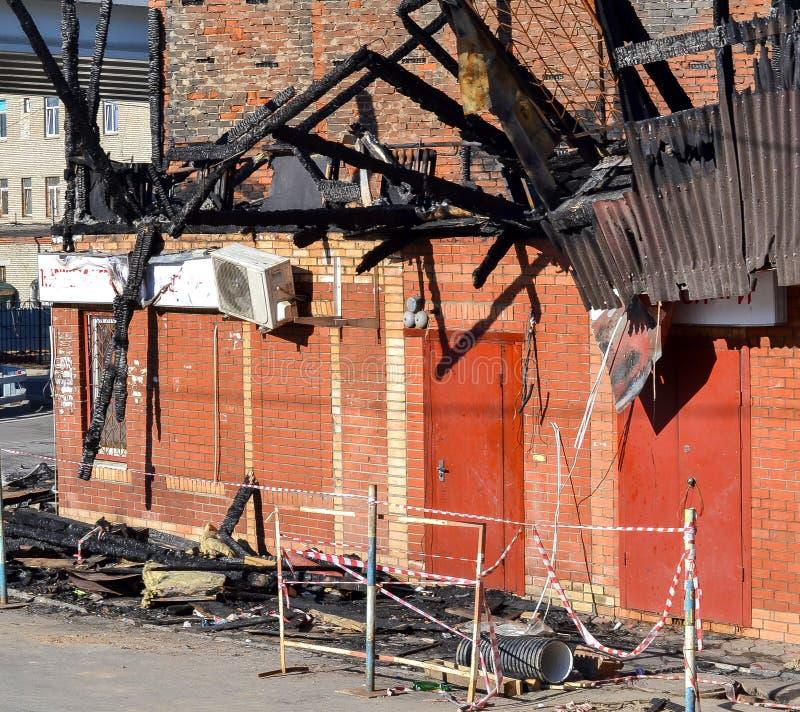 对屋顶的损伤从火 砖房子,损坏被火 检查灭火器的人 库存图片