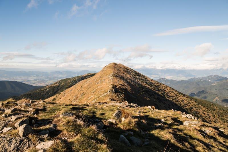对山草甸盖的Zakluky小山的看法用从波拉纳小山的少量岩石在Nizke Tatry山在斯洛伐克在秋天期间 免版税库存照片