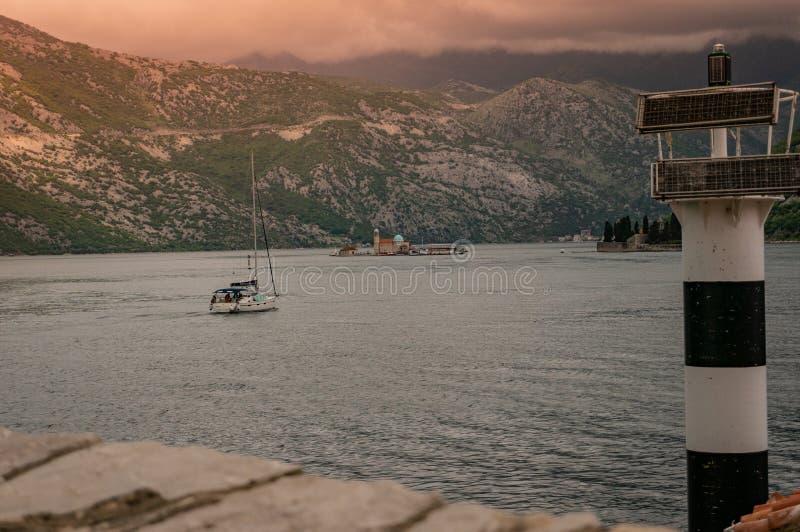 对峭壁的维尔京的灯塔的偏僻的小船航行在科托尔湾 免版税图库摄影