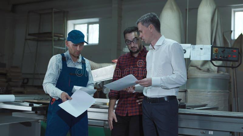 对工作者的工头解释的图纸 免版税库存照片