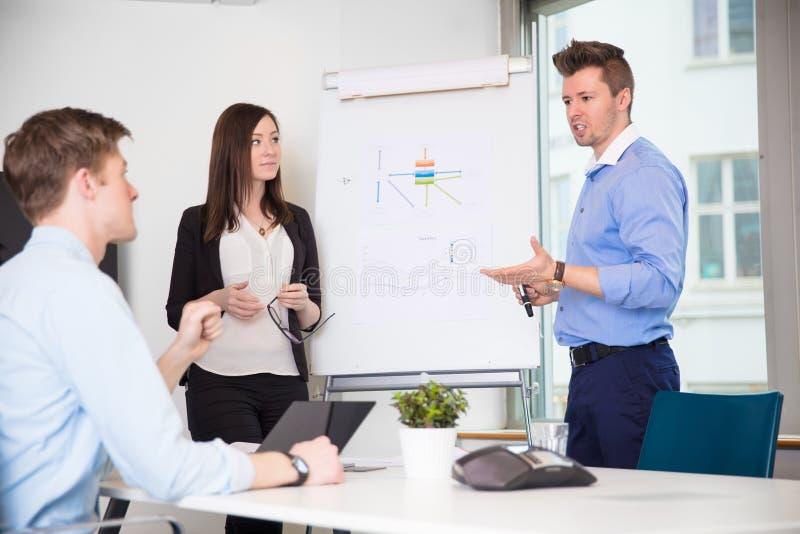 对工友的男性专业解释的图在办公室 图库摄影
