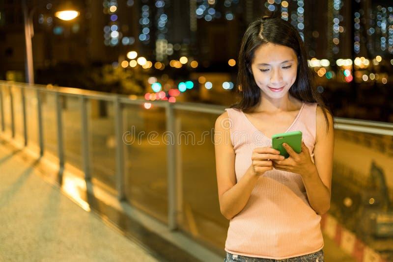 对巧妙的电话的妇女用途在城市 免版税库存图片