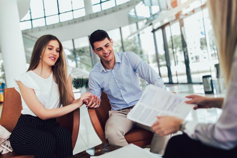 对年轻夫妇的财政顾问陈列报告他们的投资的 谈论购买的推销员和正面夫妇 免版税库存图片