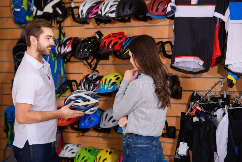 对年轻女人的微笑的男性经理陈列自行车盔甲 免版税库存照片