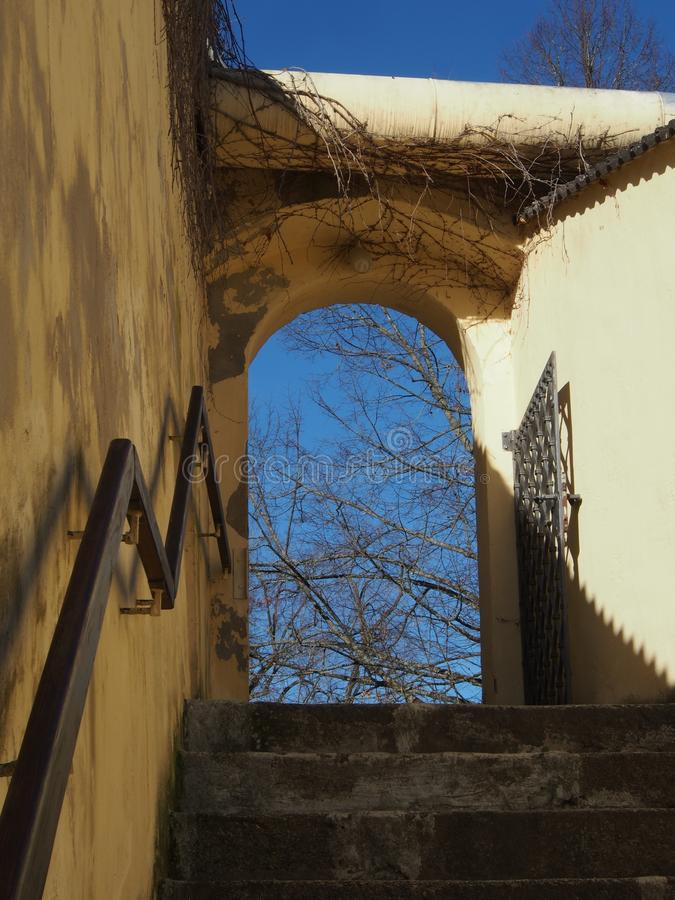 对庭院的门户有台阶、路轨和伪造的铁门的 库存图片