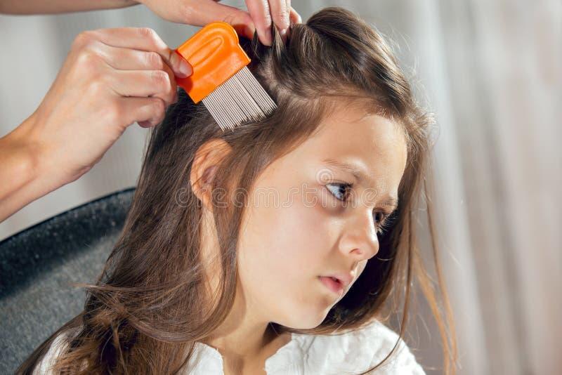 对待女儿的头发的母亲反对虱子 免版税库存照片
