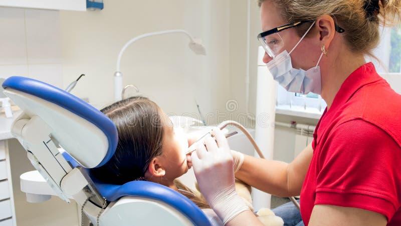 对待女孩牙的牙医特写镜头画象与牙齿钻子 免版税库存照片