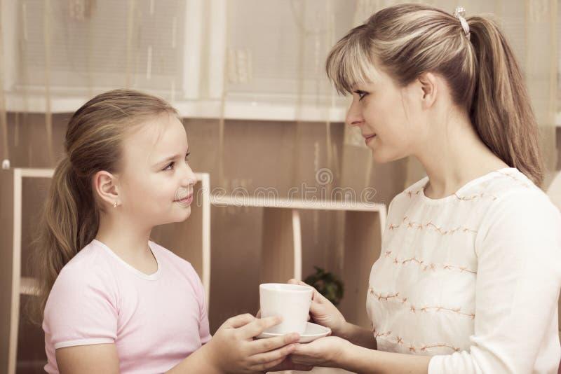 对待她的母亲的爱恋的女儿到一个杯子咖啡 库存图片