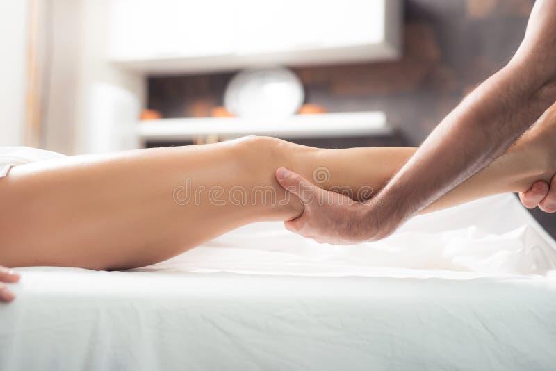 对待妇女的男按摩师与治疗按摩在温泉沙龙 免版税库存照片