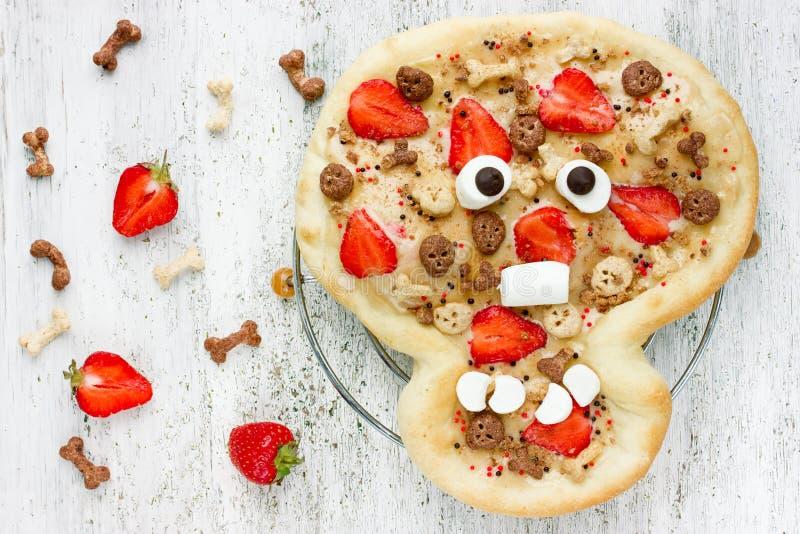 以对待孩子的滑稽的头骨的形式甜薄饼在Hallowee 库存图片