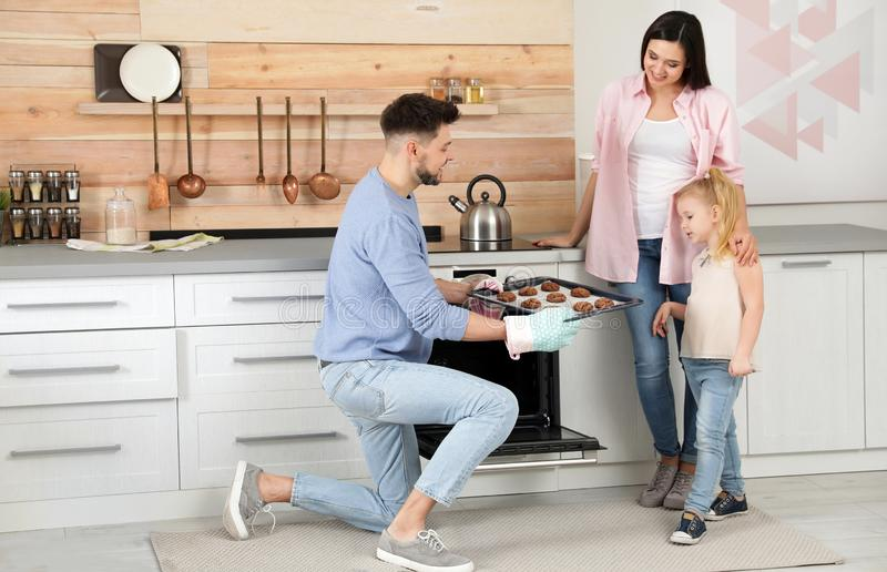 对待家庭的人与烤箱烘烤了曲奇饼 免版税库存照片