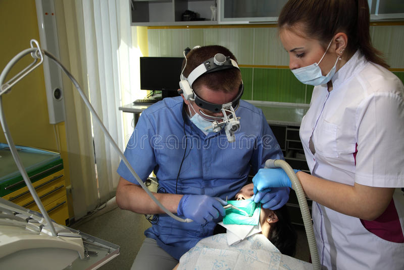 对待患者` s牙的牙医与在牙齿诊所的牙齿工具 牙科 免版税库存图片