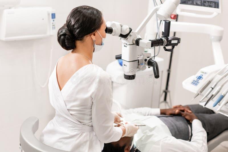 对待根管的年轻女人牙医使用在牙齿诊所的显微镜 说谎在牙医椅子的人患者与 免版税库存图片
