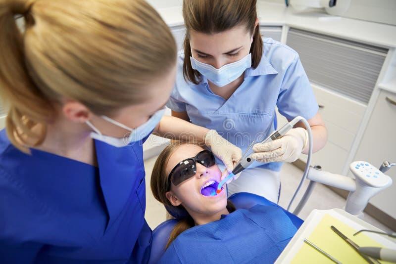 对待耐心女孩牙的女性牙医 免版税库存图片