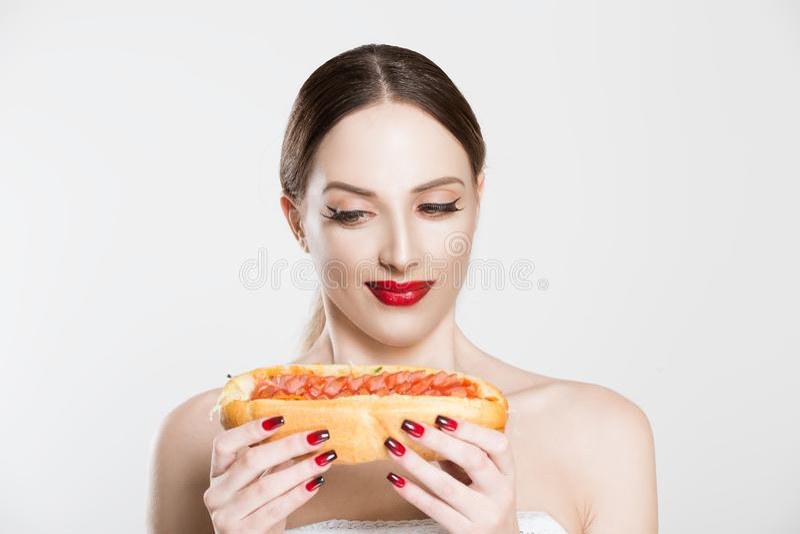 对快餐的渴望 美丽的年轻女人手里拿着美味的热狗,想不想吃,心有疑虑 免版税库存图片