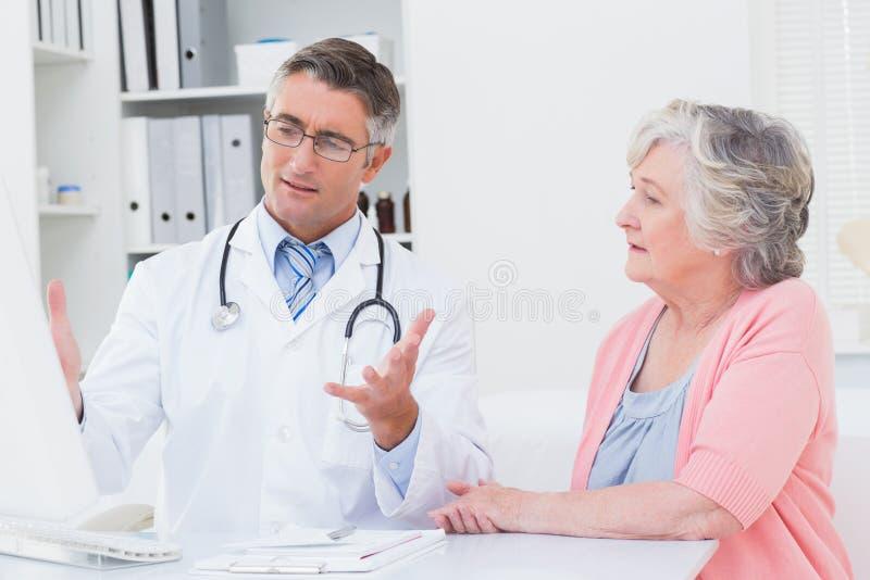 对患者的医生explaning的报告在计算机上 免版税库存图片
