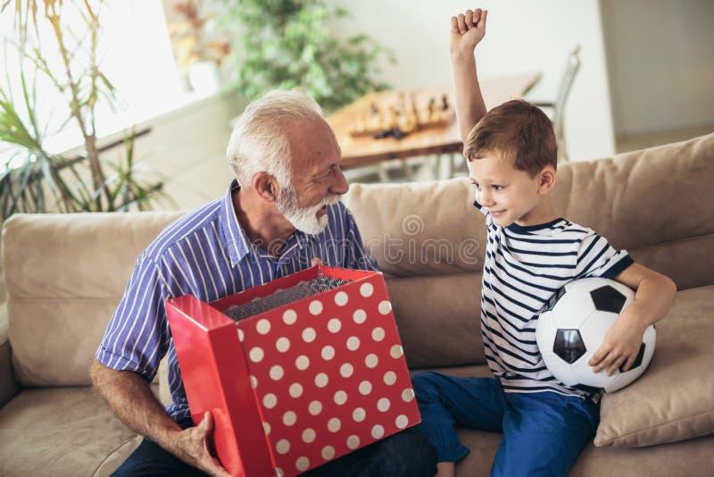 对愉快的孙子的英俊的资深祖父提出的礼物 库存图片
