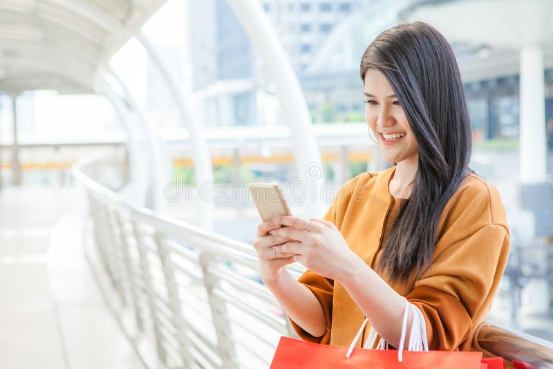 对手机和运载的纸袋的妇女用途在城市 免版税图库摄影