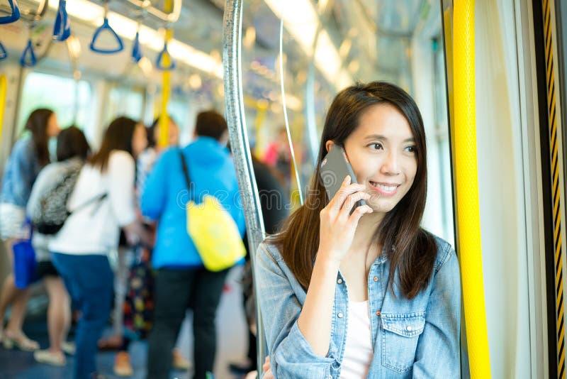 对手机的妇女谈话在火车隔间 图库摄影