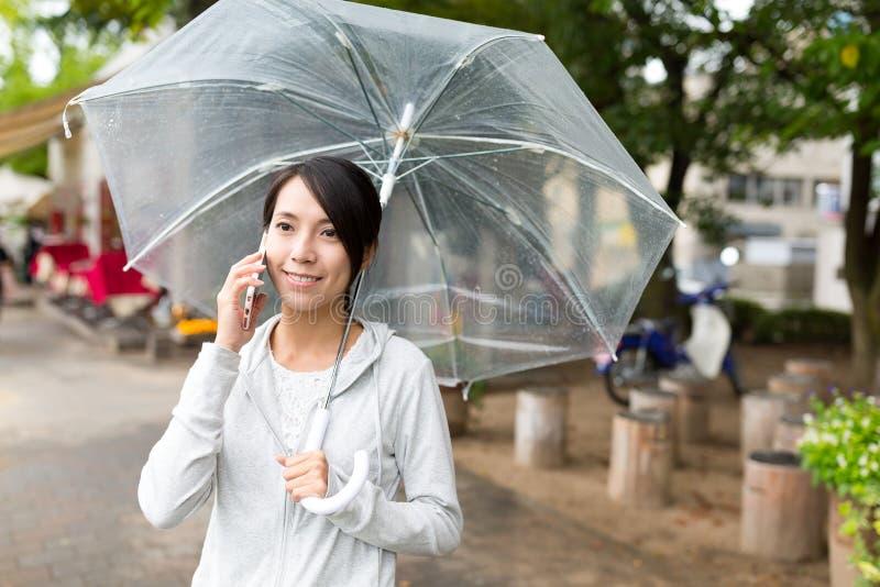 对手机的妇女谈话有伞的 库存图片