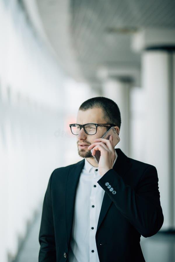 对手机的年轻商人在窗口外面的谈话和神色 免版税库存图片