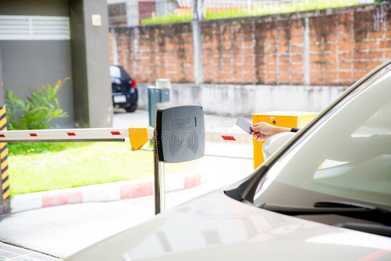 对打开停车场门的扫描器的手扶的卡片 停放的保障系统 免版税库存图片