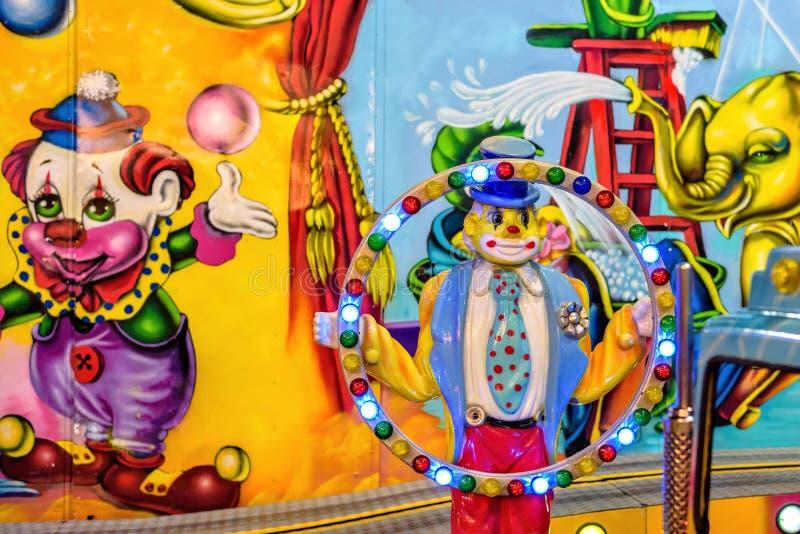 对拿着光的过山车小丑的夜视图 库存图片