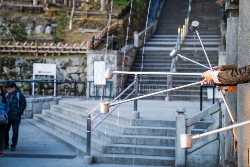 对挖出的水的接近的人手尝试从3与长的把柄杯子的圣水线在清水寺寺庙,日本 库存照片