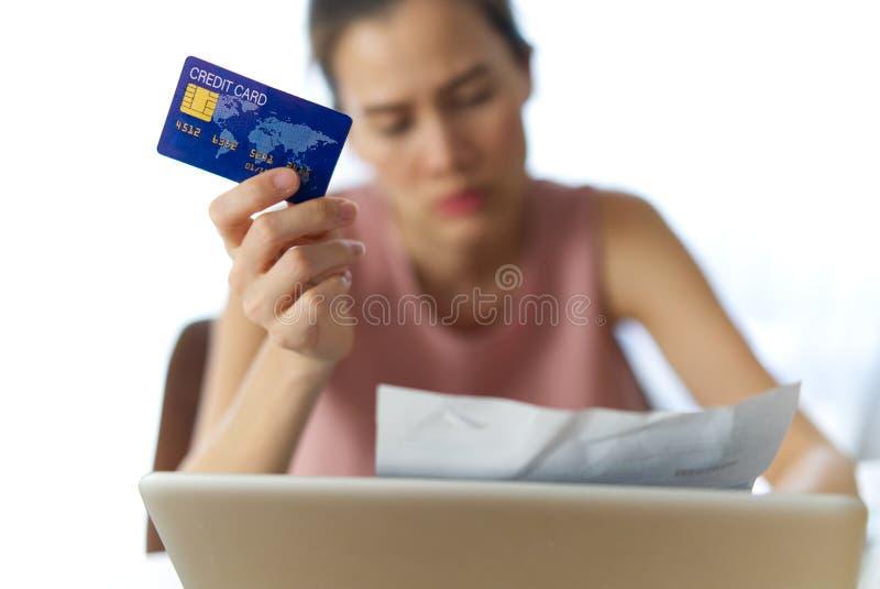 对支付信用卡债务的发现金钱的被注重的年轻坐的亚洲女孩忧虑 免版税库存照片
