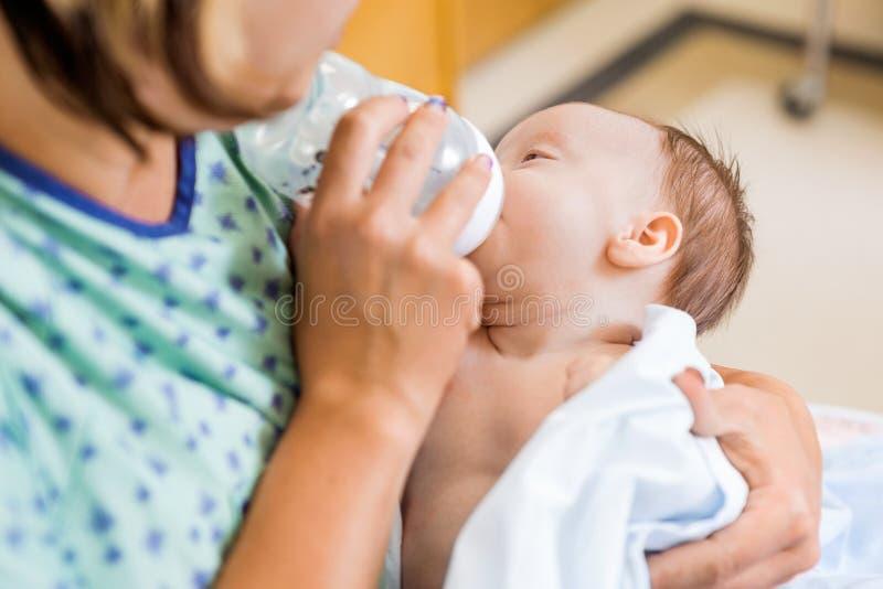 对新出生的女婴的母亲哺养的牛奶  库存图片