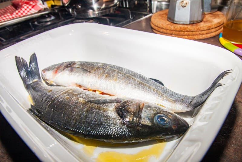 对新鲜的鲈鱼,在白色平底深锅,在橄榄油 库存照片