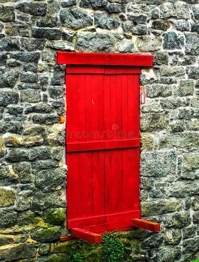 对无处的红色门:石墙 库存图片