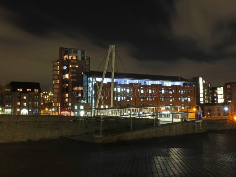 对明亮地横渡亚耳河的骑士桥梁的入口在利兹在与城市公寓和办公楼的晚上 免版税图库摄影