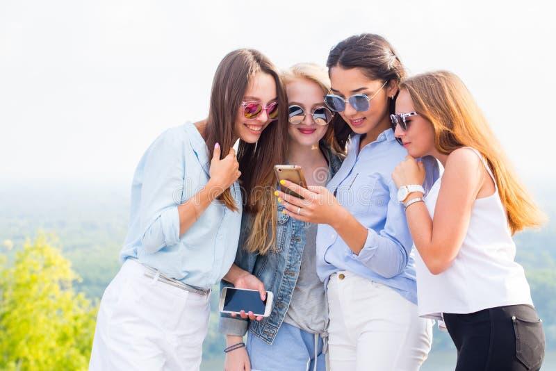 对智能手机、互联网、应用和消息的用途 一个小组美丽的女孩看电话女朋友和笑, 免版税库存图片