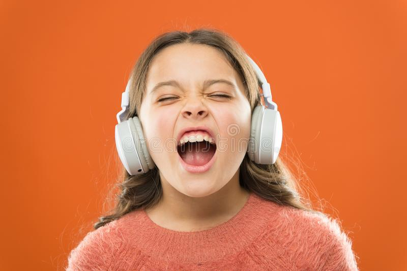 对更好的声音表现 可爱小儿童做声音在歌曲 听音乐和唱歌的女孩 库存照片