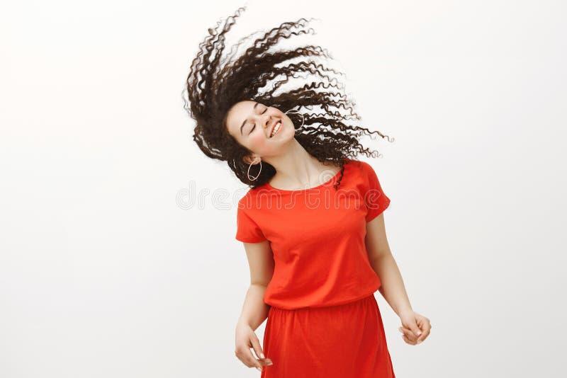 对最充分的愉快的正面可爱的女孩的生存生活时髦的红色礼服的,有闭合的眼睛的挥动的卷发和 免版税库存图片