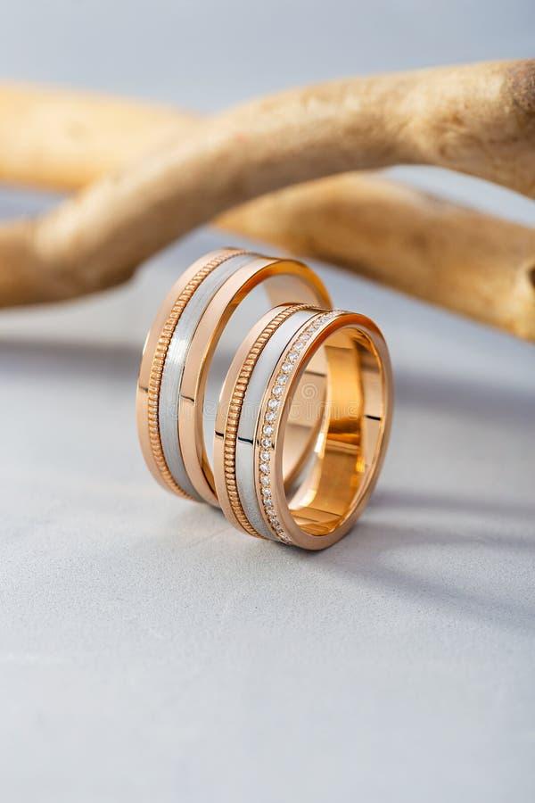 对有金刚石的金结婚戒指在与木头的灰色背景 免版税库存照片