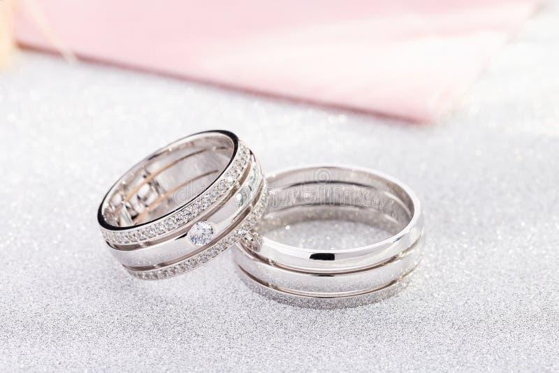 对有金刚石的银色结婚戒指在白色光滑的背景 免版税库存照片
