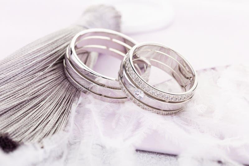 对有金刚石的银色结婚戒指在粉红彩笔背景的女性圆环谎言 库存照片