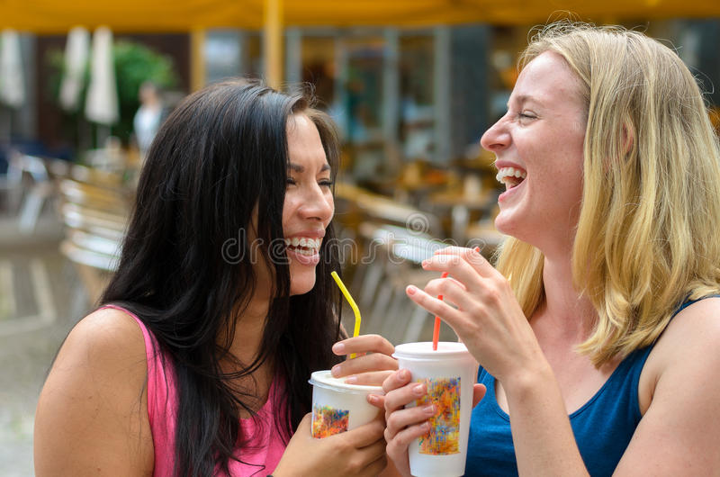 对有饮料的愉快的妇女,当笑时 免版税库存图片